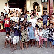 Glückliche Kinder stehen vor dem Haus.